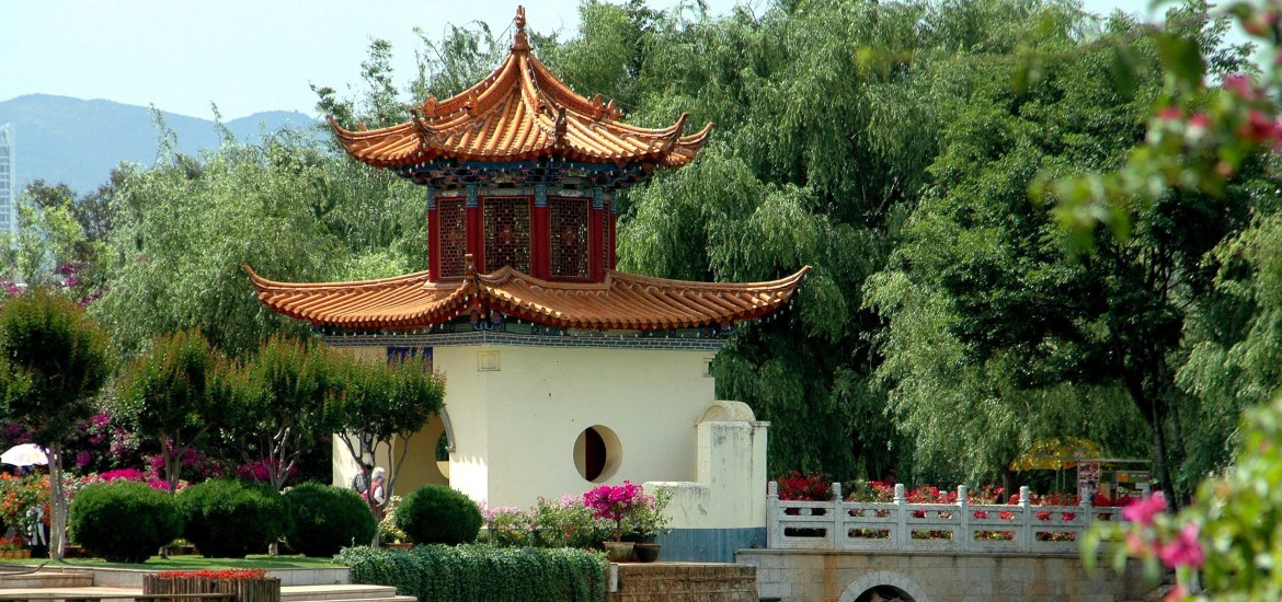 The Passing Gate pavilion with tiled flying eave roofs leads to a small bridge lined with colourful Bouginvillea flowers in lush Daguan Park in Kunming, China