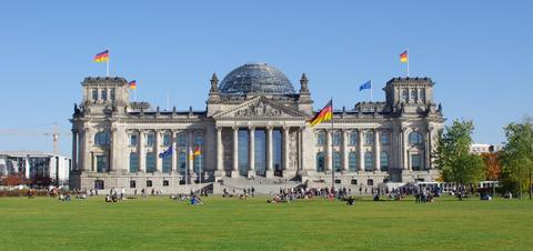 Tourists on the lawn of the Reichstag Building in Berlin, Germany