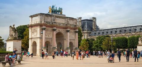 Tourists walk near The Triumphal Arch in front of the Louvre Museum
